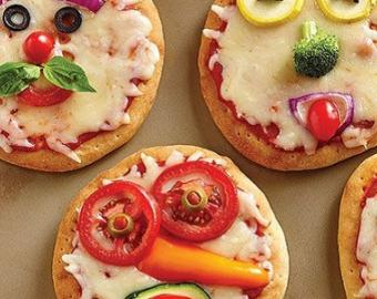 Four mini pizzas decorated with vegetables